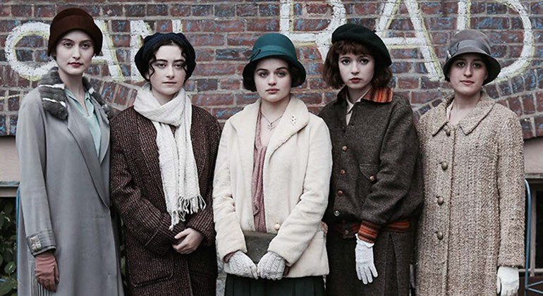 Five women wearing 1920's period clothing standing in a line in front of a brick building.