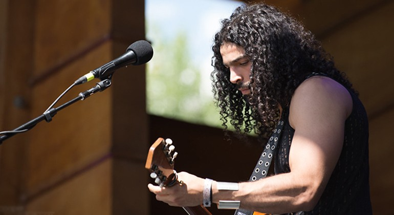 Ramy Essam playing guitar during a performance
