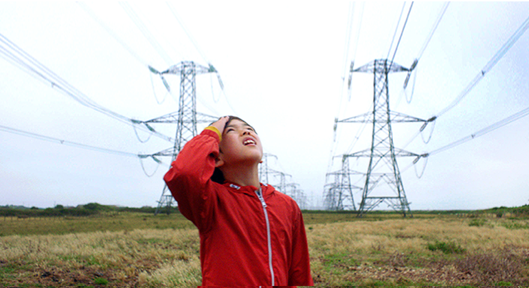 A child in a red jacket squinting up at the sky while standing in a field with tows of transmission towers in the background.