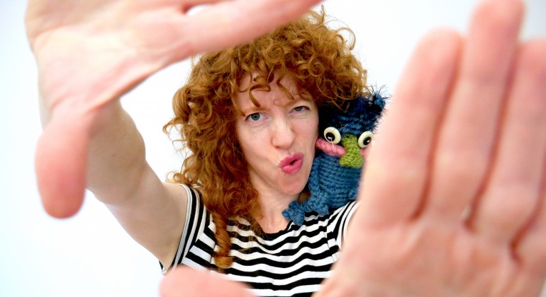 A feminine presenting person with red curly hair and a black and white striped shirt holds their hands up in front of the camera, with a crochet doll on their shoulder
