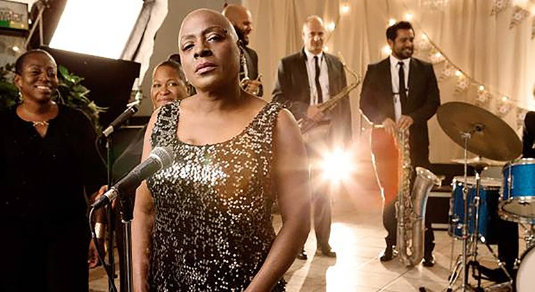 Sharon Jones in front of a microphone with a band behind her