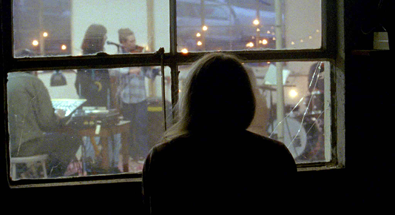 A figure in the dark looks into a brightly lit window where a group of musicians are practicing.