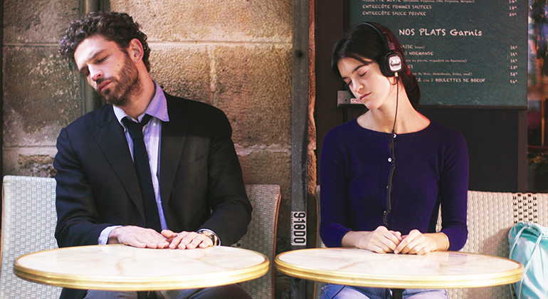 A man and a woman sitting next to each other at separate small cafe tables, with their heads turned to the same side and their eyes closed.