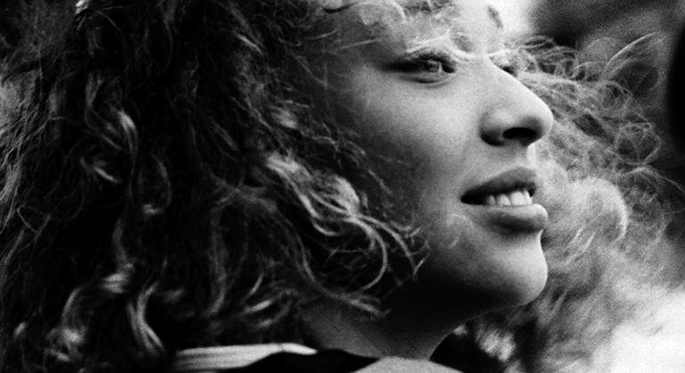 A close up, black and white portrait of a woman with short curly hair turning her head back towards the camera while smiling.