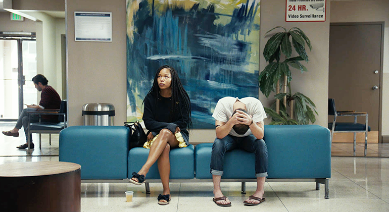 Two people sitting on a modern blue couch in a lobby, with a large blue and green abstract painting directly behind them. One person is looking ahead and the other has their head in their hands.
