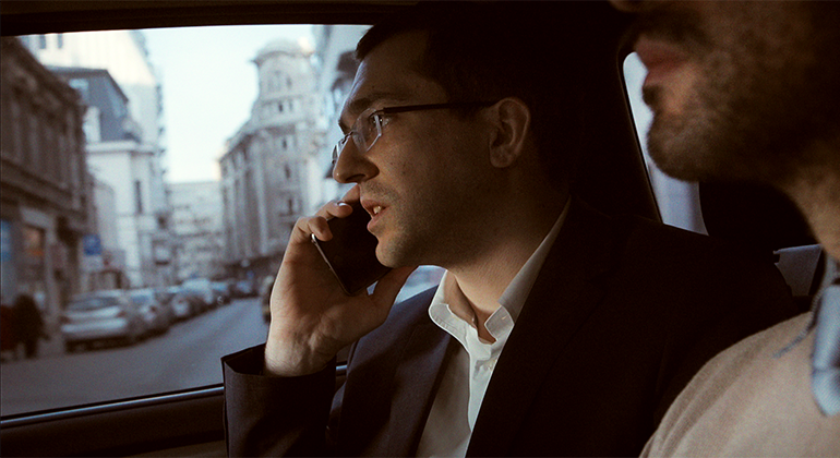 Two masculine presenting people in a car driving down a city street. The person we see most clearly is wearing a suit and glasses and talking on a cell phone.
