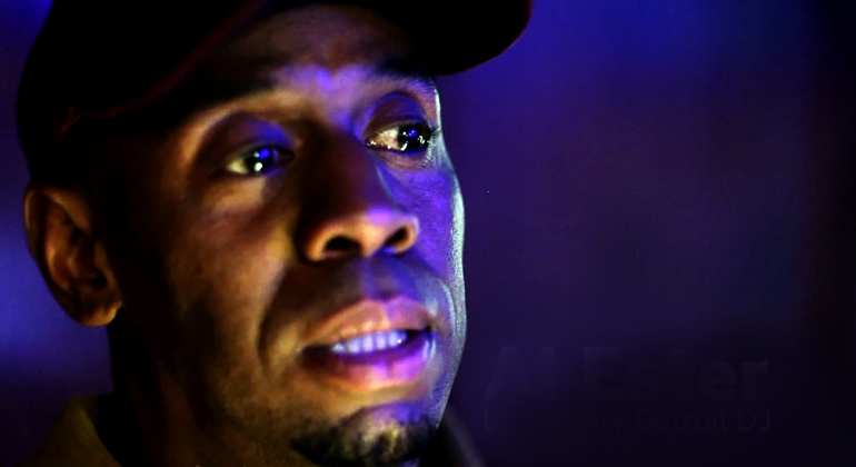 The face of a man in a dark room with a bright purple light reflecting on his face