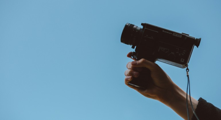 A hand holding a small video camera against a solid pale blue background