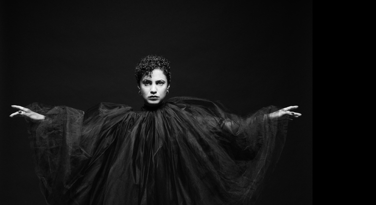 A black and white image of a woman in a voluminous black tulle dress that reaches from high on her neck down to her outstretched hands, reaching out to either side.