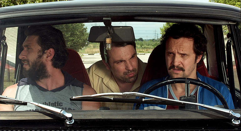 Two men sit in the front seats of a vehicle while another man in the backseat sticks his head in between them as they all engage in conversation.