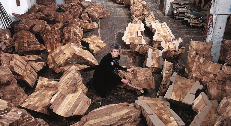 Ursula von Rydingsvard inspecting large sections of wood for her sculptures