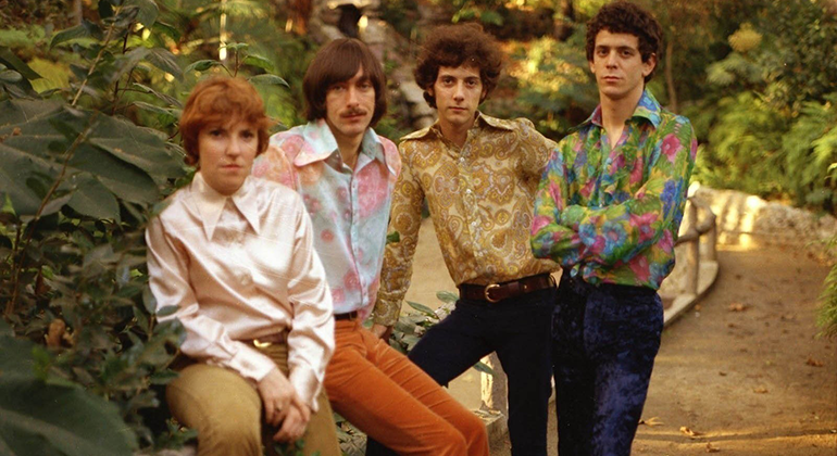 The four members of The Velvet Underground pictured standing in paisley shirts and jeans in a wooded area.