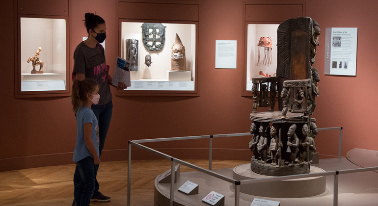 Woman and child wearing masks in the African Art galleries at the Detroit Institute of Arts