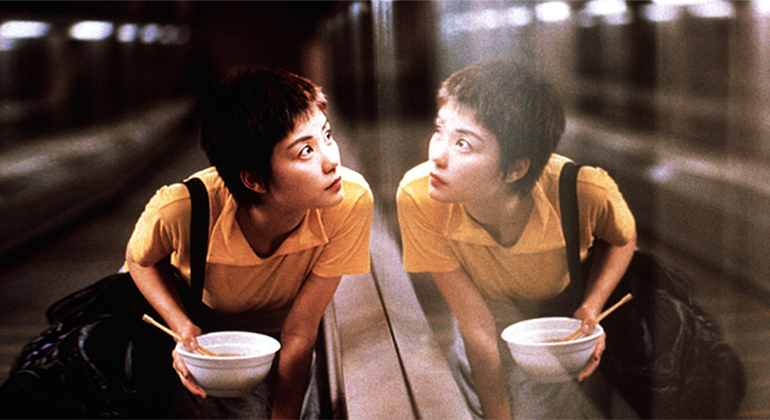 A feminine presenting person with short, spiky hair and wearing a collared, yellow shirt, holds a white bowl with chopsticks. They are staring into their reflection in a large window.