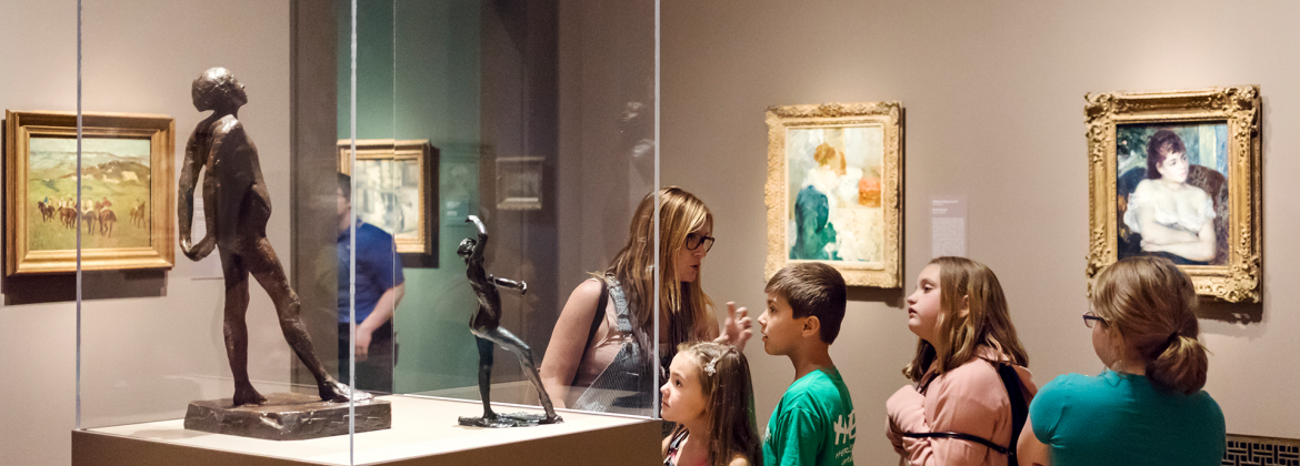 A family viewing a Degas sculpture in Humble and Human: Impressionist Era Treasures