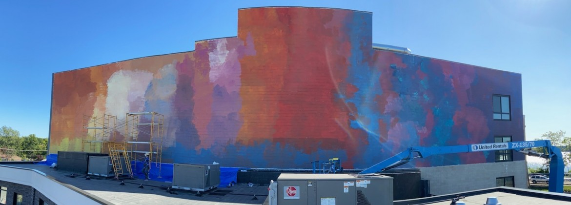 The Lake Orion PIPA mural, an abstract painting of different clouds of colors ranging from red, orange, yellow, purple and blue, as seen from a short distance