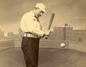 Baseball card of Dan Brouthers in uniform swinging a bat at a ball flying towards him