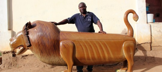 Coffin artist Paa Joe standing with a coffin in the shape of a lion