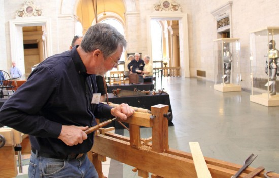 A man working on wood furniture in the Great Hall