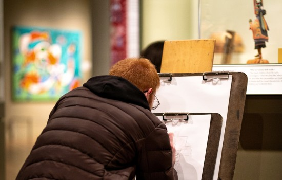 A person hunched over a bench and drawing in the Native American galleries