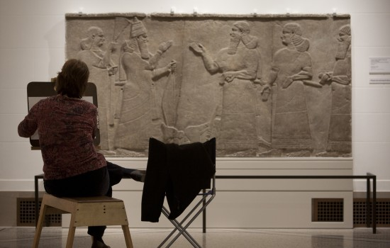 A woman drawing in front of a slab in the Islamic gallery