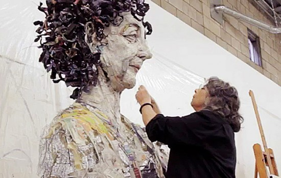 A woman carefully working on a large mural
