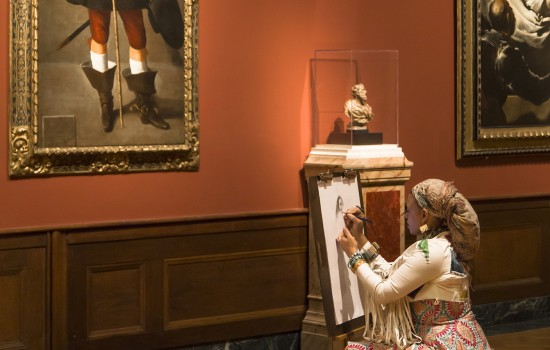 A woman sitting and drawing in a renaissance art gallery