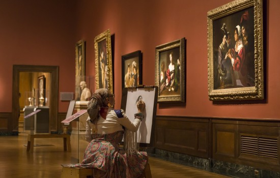 Woman sitting at an easel and drawing in the Medieval & Renaissance galleries at the Detroit Institute of Arts