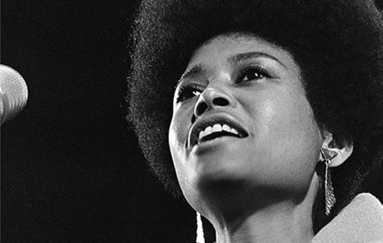 Close-up black and white photo of Abbey Lincoln in 1966 showing her singing into a microphone with a small, round afro and dangling triangular earrings.