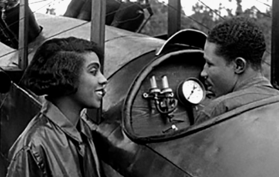 A woman speaking to a man who's sitting in a small plane