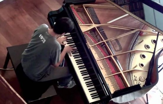 An aerial photograph of Andre Mehmari playing piano