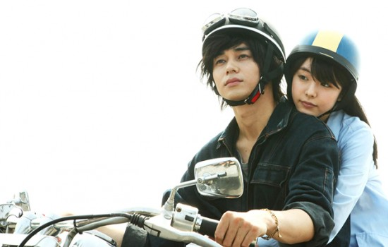 A still from the movie Asako I & II with a Japanese man and woman on a motorcylce