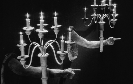 A black and white image of two candelabras with two disembodied arms.