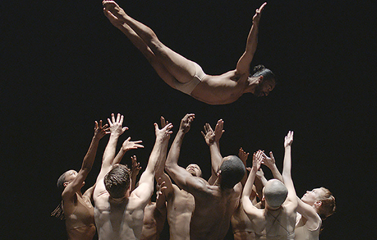 A group of dancers in skin toned clothes hoisting a dancer up in the air above them.