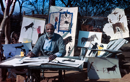Bill Traylor pictured sitting at a desk outside with his paintings hanging up in the trees behind him.