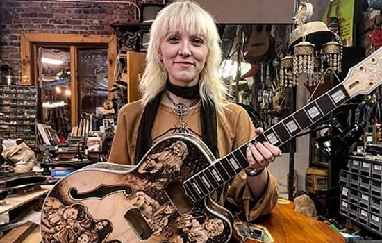 A blond woman holding a guitar in a music shop