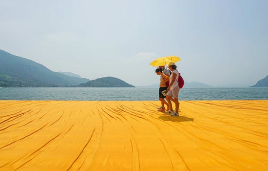 Three people walking on a yellow beach with yellow umbrellas