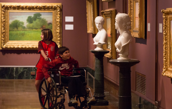 Two children in the American Gallery, one in a wheelchair and the other helping them
