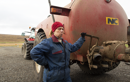 A woman in a dirty blue boiler suit scowls at the camera while standing next to a large red tractor.