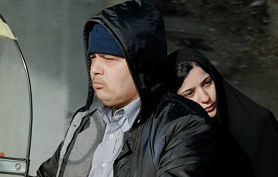 A man in a black hooded jacket stares off camera as a woman in a black headscarf leans against his back, facing the camera.