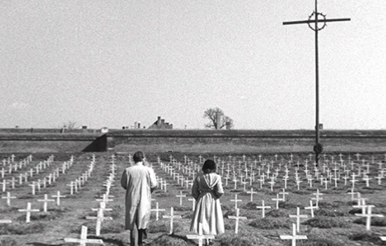 Two people walking through a large cemetery with even rows of crosses lined up and one large cross in the background.
