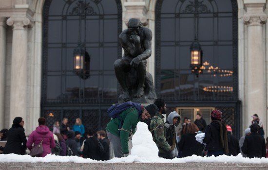 A small snowman in front of the thinker