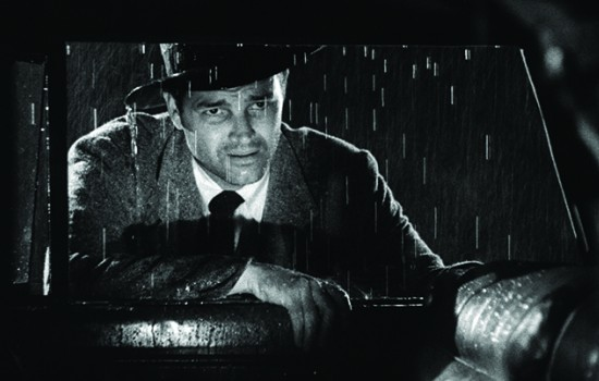 A man looking into a car window while standing in the rain
