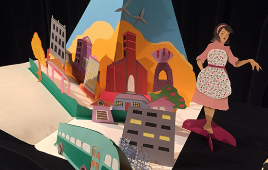 A colorful paper town with a paper bus and a paper 1950s housewife.