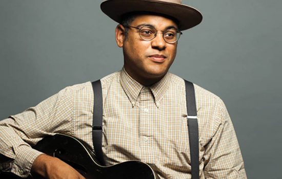 Don Flemmons in a flat brimmed hat and suspenders, posing with a guitar