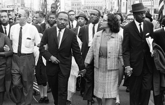 An image of Dr. and Mrs. King walking hand in hand through the streets with other Civil Rights leaders