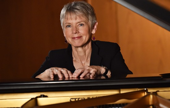 Ellen Rowe photographed behind a piano
