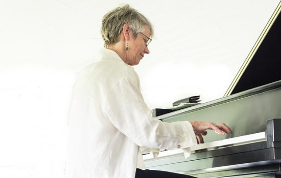 Ellen Rowe, sitting at a piano in a large white button down shirt and short hair with a bright white background.