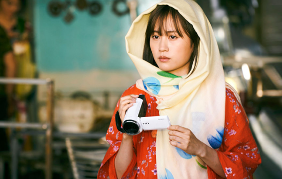 A woman wearing a scarf over her head and holding a handheld video camera with a worried look on her face.