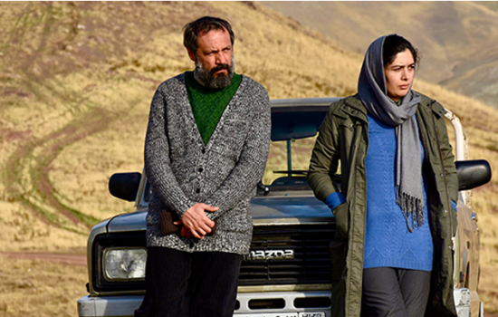 Two people leaning against the front of a Mazda suv and staring at something off camera.
